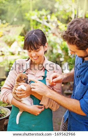 Couple of young people caring about the dog (focus on the eyes of woman) - stock photo