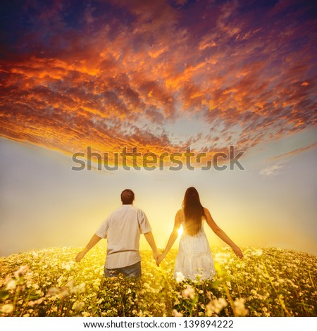 couple of young people holding hands and walks away into the sunset - stock photo