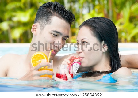 Couple of young people in swimming pool drinking juice - stock photo