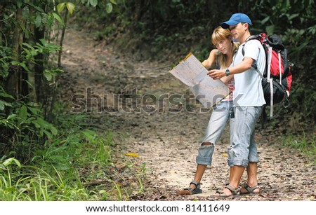 Couple of young people looking at the map in the forest - stock photo