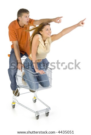 Couple of young people riding by trolley. Having fun. Boy looking surprised.  Isolated on white in studio. Side view