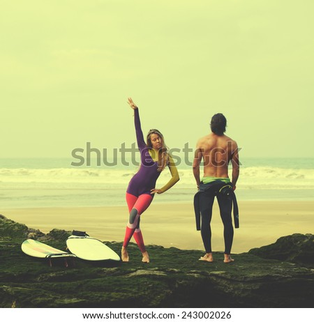 Couple of young professional surfers having fun standing against amazing ocean view, filtered image - stock photo