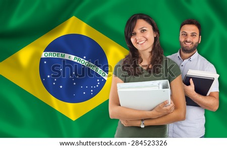 Couple of young students with books over brazilian flag - stock photo