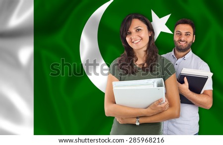 Couple of young students with books over pakistan flag - stock photo