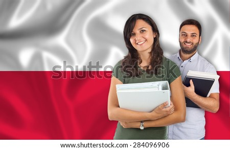Couple of young students with books over polish flag - stock photo