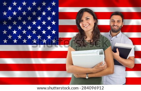 Couple of young students with books over United States flag - stock photo