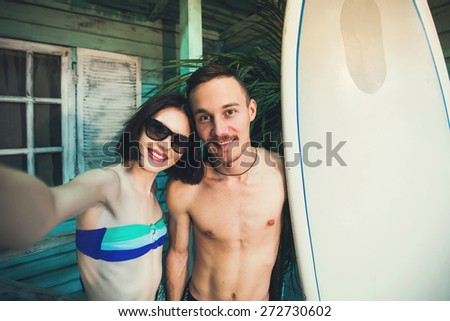 Couple of young surfers in love taking selfie picture at beach house at ocean side - stock photo