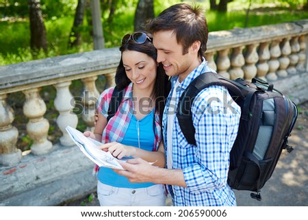 Couple of young travelers studying map of ancient town - stock photo
