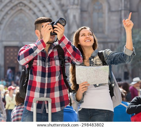 Couple of young travellers a man and a woman in casual clothes with backpacks on their backs are sightseeing with a map and photographing places of interest - stock photo