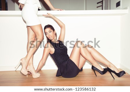 couple of young women in elegant dresses and high heel shoes indoor shot - stock photo