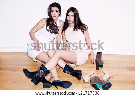 couple of young women with lots of shoes on the floor - stock photo