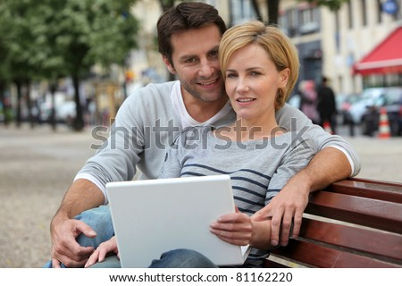 couple on a bench with laptop - stock photo