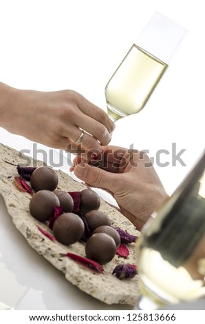 Couple on a date both holding the same glass of wine. White table and background. - stock photo