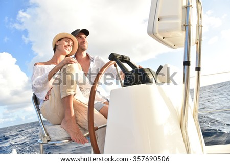 Couple on a sailboat sitting at wheel - stock photo