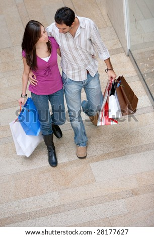 Couple on a shopping centre with bags - stock photo