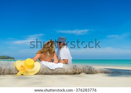 Couple on a tropical beach at Maldives sitting