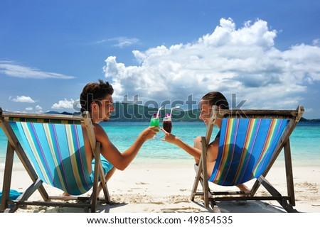 Couple on a tropical beach in chaise lounge - stock photo