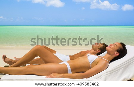 Couple on a tropical beach relaxing at the chair