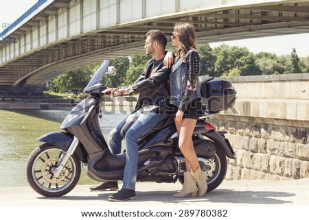 Couple on a vespa by the river - stock photo