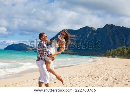 Couple on beach having fun in summer. Woman and man smiling happy on beach on Hawaii.  - stock photo