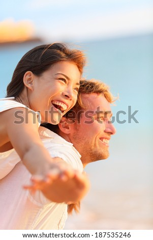 Couple on beach having fun laughing in love on romantic honeymoon travel vacation summer holidays romance. Young happy lovers, Asian woman and Caucasian man doing joyful piggybacking ride outdoors. - stock photo