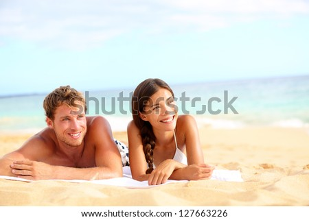 Couple on beach looking happy during summer travel vacation holidays. Multiracial young couple lying in sand on beach on looking to side. Asian woman, Caucasian man. - stock photo