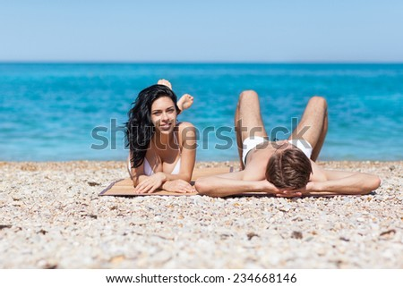 Couple on beach, lying romantic man and woman sea shore, summer ocean vacation holiday blue sky - stock photo