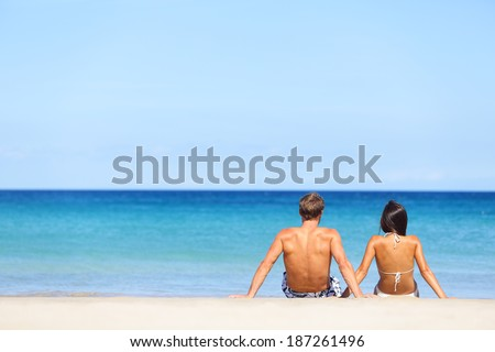 Couple on beach sitting in sand looking at sea enjoying summer holidays travel on tropical beach with blue water. - stock photo