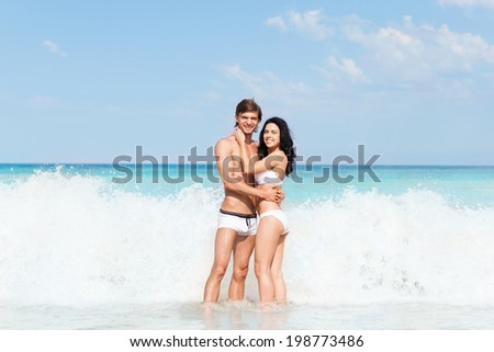 Couple on beach standing in storm water wave foam, Young happy man and woman embrace at sea shore romantic smiling, summer ocean vacation holiday