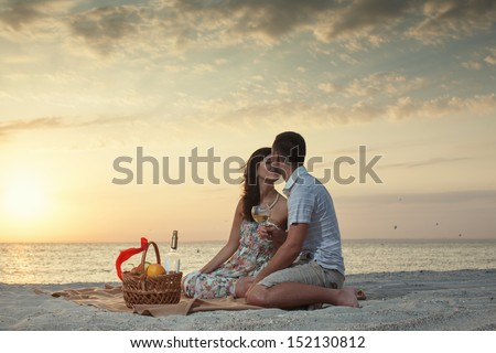 Couple On Beach With Luxury Wine Picnic during beautiful sunset. Dawn - stock photo