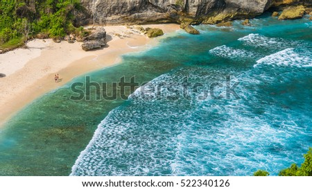 Couple on beautiful Atuh Beach with White Long Waves, Nusa Penida, Bali, Indonesia