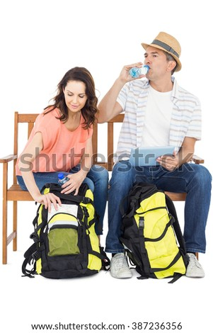 Couple on bench using tablet on white background