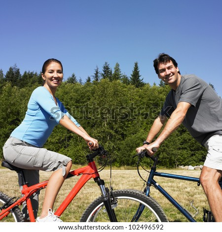 Couple on bicycles in rural area - stock photo