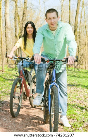 Couple on bike relaxing outdoors.