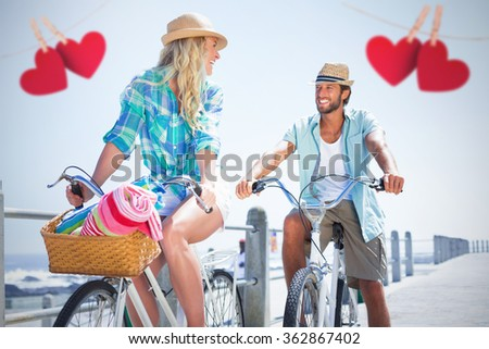 Couple on bike ride by the beach against hearts hanging on a line - stock photo