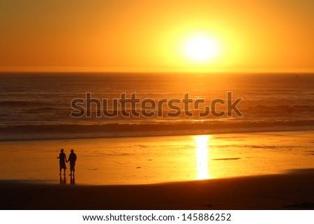 Couple on California Beach at Sunset - stock photo