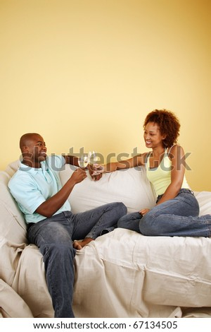 Couple on couch toasting with white wine - stock photo