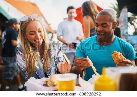 couple on date eating pickles and drinking beer having fun