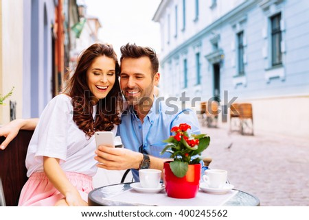 Couple on european vacation sitting in outdoors cafe looking at phone - stock photo