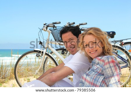 Couple on holiday sitting in front of bicycles - stock photo