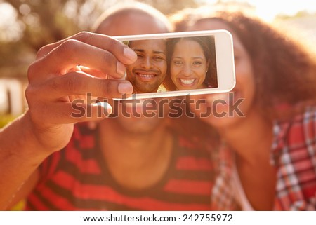 Couple On Holiday Taking Selfie With Mobile Phone - stock photo