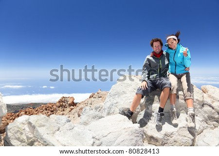 Couple on mountain top of volcano Mount Teide, Tenerife after hiking to summit. Woman showing thumbs up success sign. - stock photo