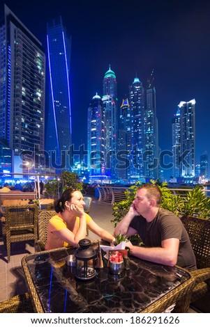 Couple on romantic dinner in Dubai marina at night - stock photo