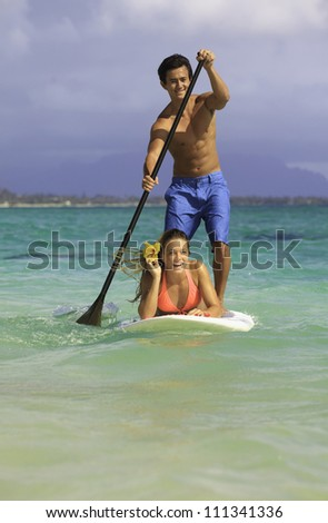 couple on stand up paddle board in hawaii