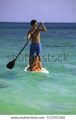 couple on stand up paddle board in hawaii - stock photo