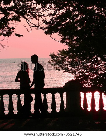 couple on the beach at pink sunset (sunrise) - stock photo