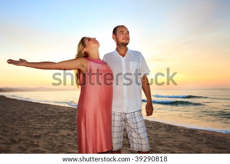 Couple on the beach at sunrise time.