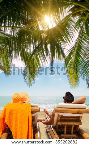 Couple on the beach at tropical resort Travel magazine concept - stock photo