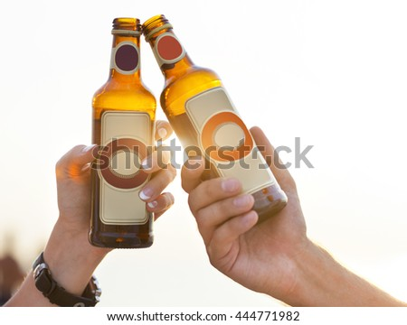 Couple on the beach having party, drinking and having fun in the sunset holding bottles in their hands with the sun shining through - stock photo