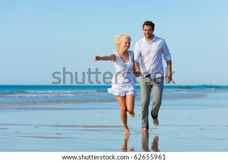 Couple on the beach in white clothing running down, they might be on vacation or even honeymoon - stock photo